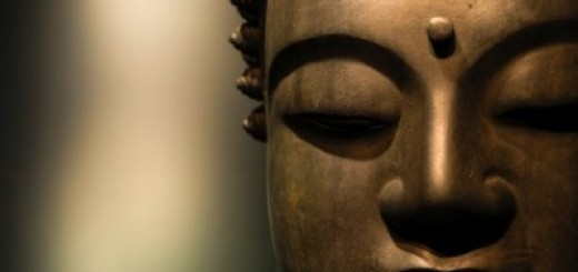 A close up of a bronze Buddah's face.